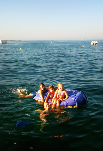 Girls on dinghy swimming in the Mediterranean sea