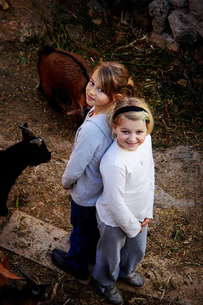 Girls visiting a farm with goats, chickens and ducks in Mgarr, Malta