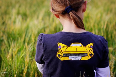 Girl standing with her back to the camera in a green field of wheat. She has a bright yellow car printed on the back of her t-shirt