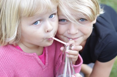 Two pretty girls sharing a drink on their summer holiday in Sweden